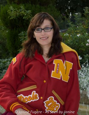 Nicole Letter Jacket sitting by fountain waist up