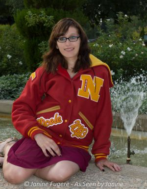 Nicole Letter Jacket sitting by fountain full pose
